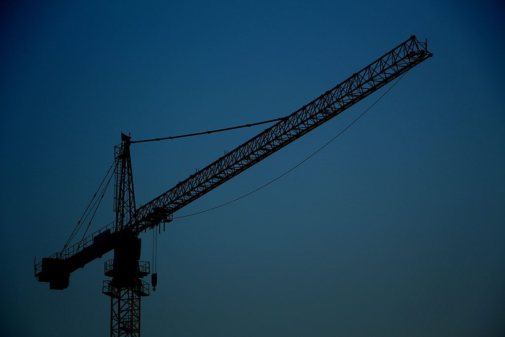 A crane at dusk. Advice to construction transactions