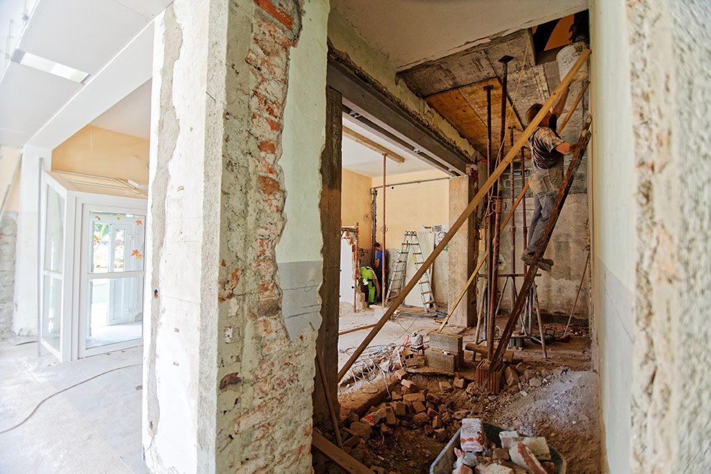 A renovation apartment, a handyman on a ladder and renovators at work. Urban renewal