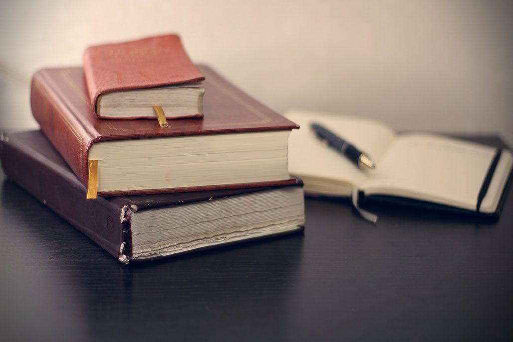 ערימת ספרים ישנים ומחברת פתוחה עם עט.