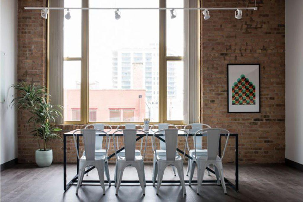 שולחן פינת אוכל בלופט עם קיר לבנים אדומות, תאורה תעשייתית, חלון, תמונה ועציץ.