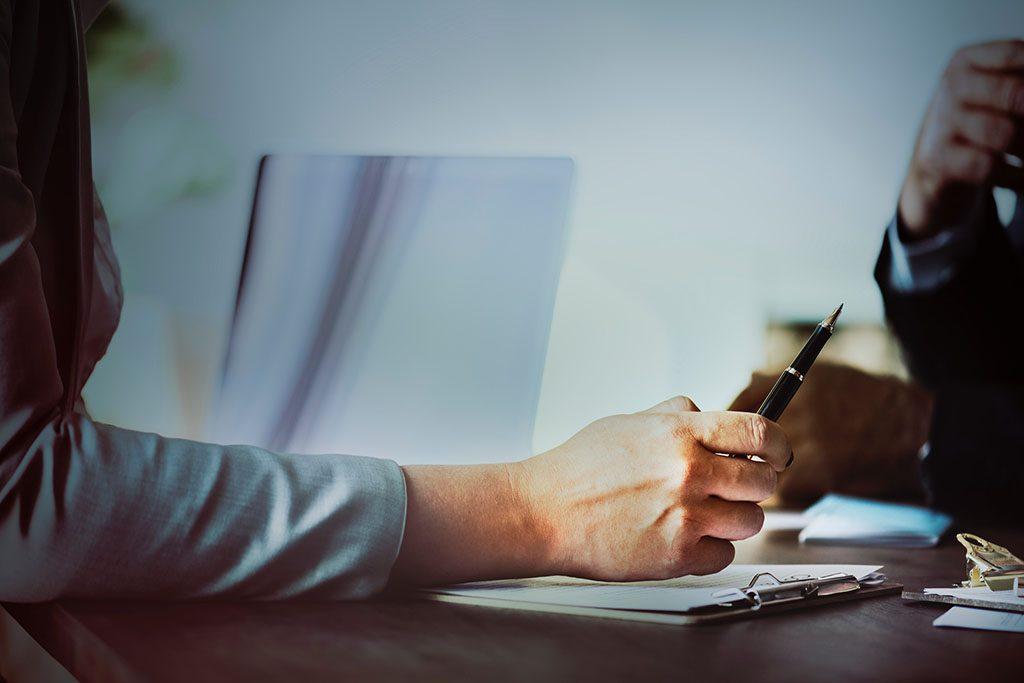 יד של עורכת דין אוחזת בעט בפגישה עם לקוח
